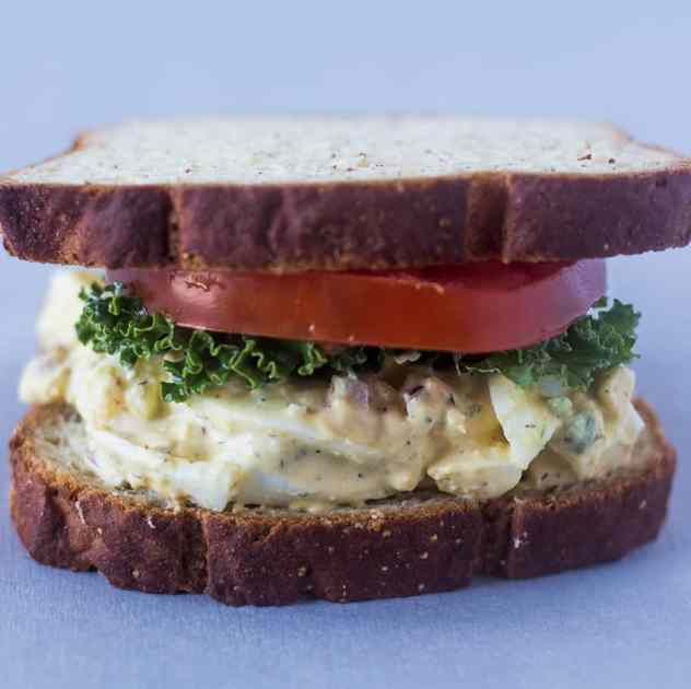 Egg Salad on a sandwich with lettuce and tomato.