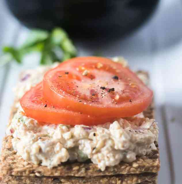 Mock Tuna Chickpea Salad on a cracker topped with tomato slaie with parsley and a black bowl in background.