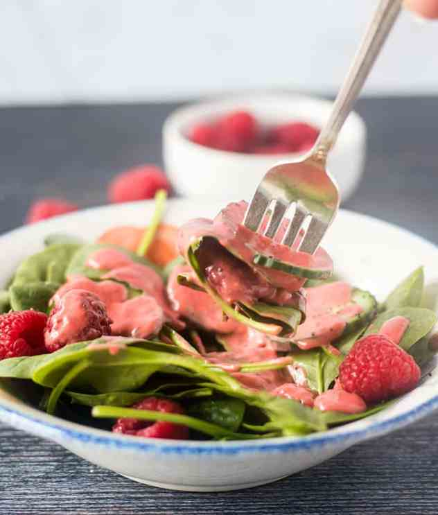 Spinach salad with raspberry vinaigrette on a silver fork with raspberries in a white bowl in the background.