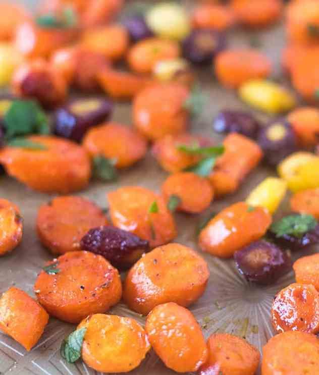 Multi colored maple glazed carrots on a sheet pan garnished with fresh parsley