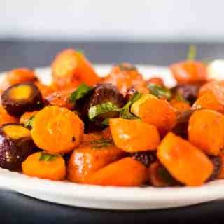 Multi colored maple glazed carrots on a white plate garnished with fresh parsley