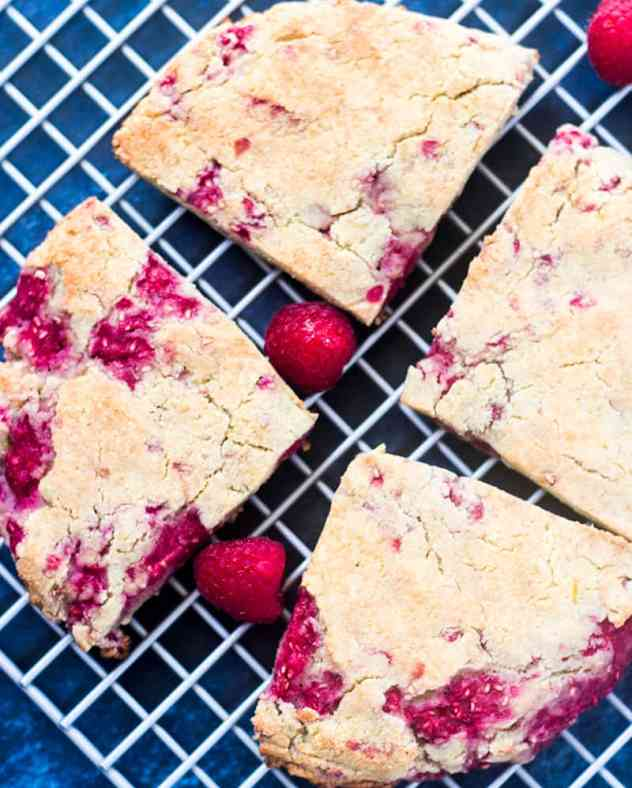 Raspberry Scones on a cooling rack with fresh raspberries.