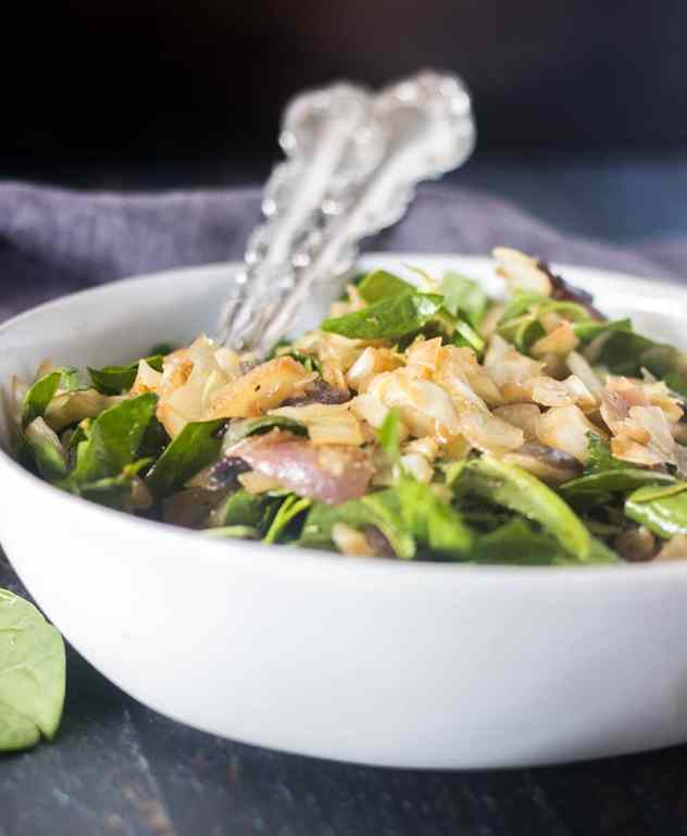 Caramelized Cabbage and Spinach salad in a white bowl with silver serving utensils.