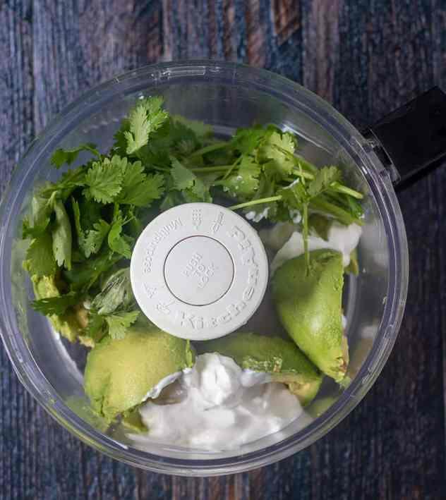 Avocado, greek yogurt, garlic, cilantro in food processor.