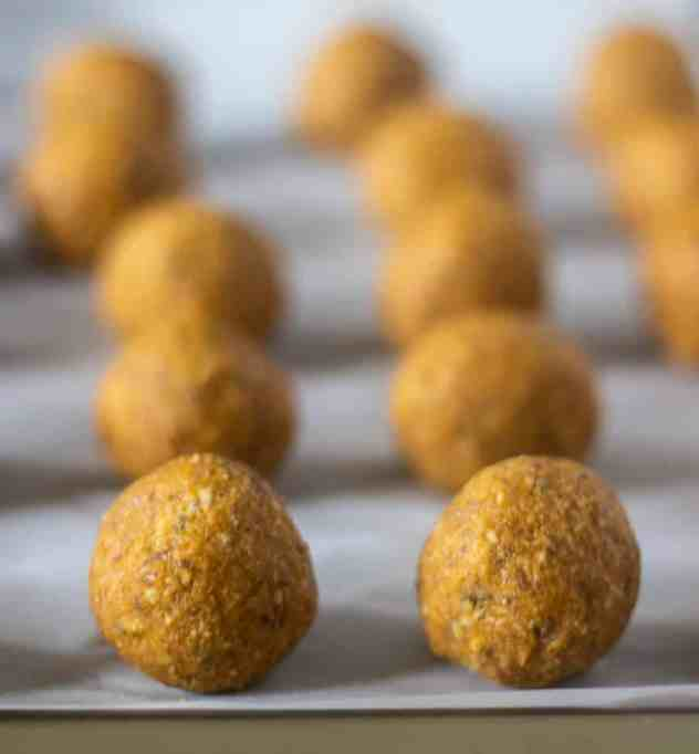 Pumpkin pie energy balls on a baking sheet lined with parchment paper