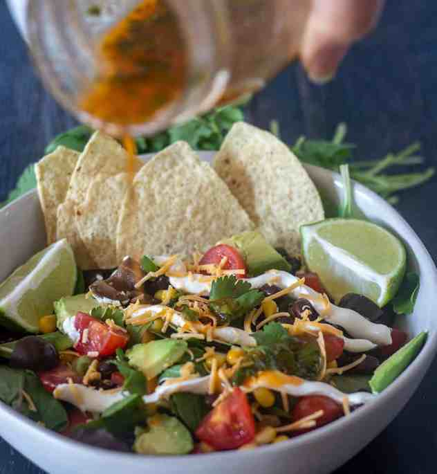 Pouring chili lime dressing on Black Bean Taco Salad