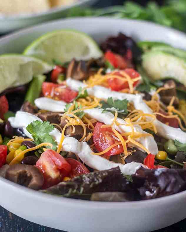 Black Bean Taco Salad in a white bowl with toppings