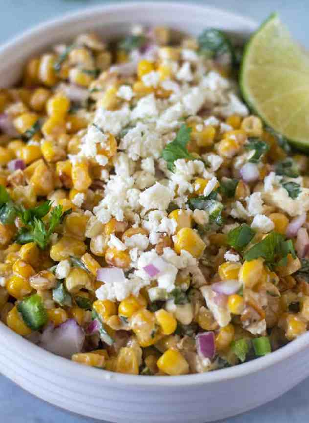 Mexican Street Corn Salad in a bowl topped with feta cheese.