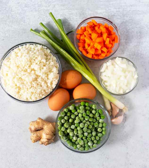 Cauliflower rice, diced carrots, diced onion, peas, garlic cloves, eggs, scallions, ginger root