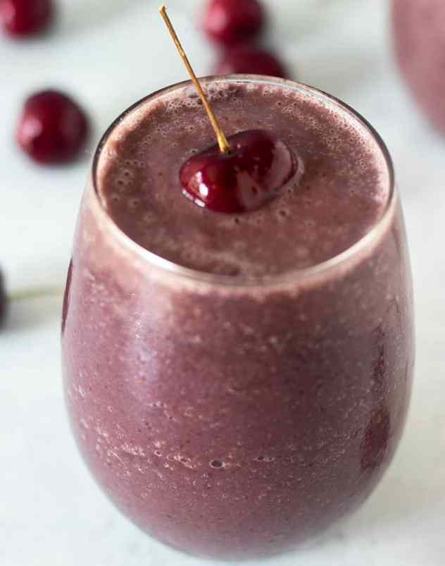 Cherry Smoothie in glass with cherry on top and cherries in background