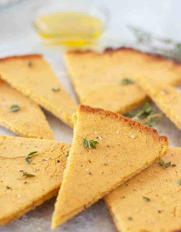 Socca on a plate cut in wedges with fresh herbs and a bowl of olive oil for dipping.