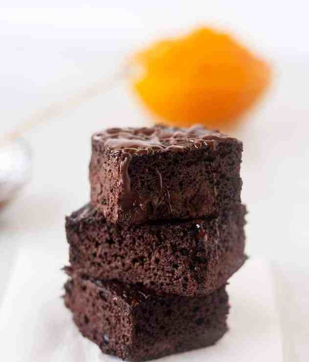 pumpkin brownies stacked with bowl of pumpkin in the background