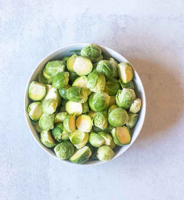 brussel sprouts in a bowl that have been trimmed and sliced in half.