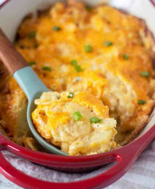cheesy scalloped potatoes in a pan with a spoon