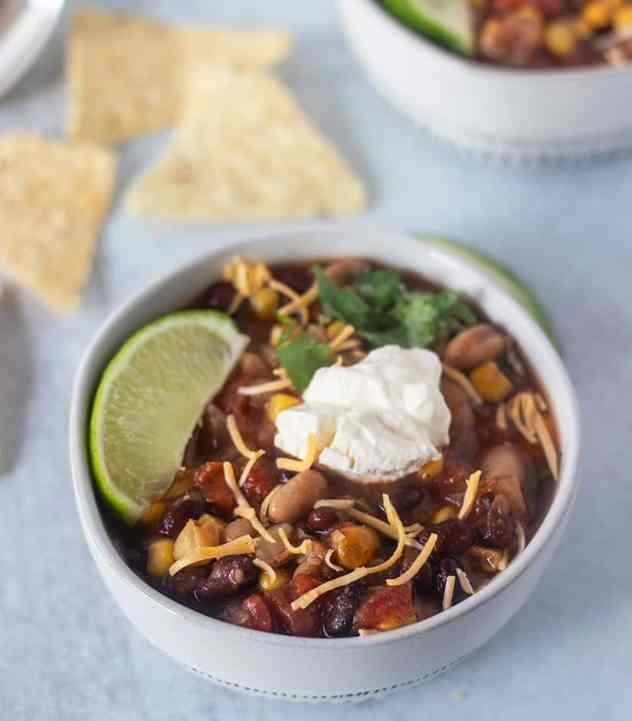 Slow Cooker Taco Soup in a bowl with a lemon wedge, cheese and sour cream.