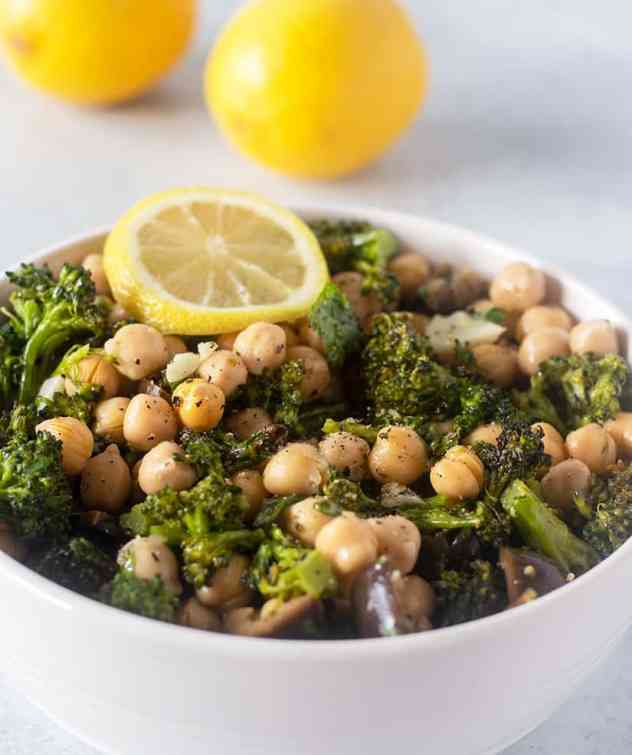Broccoli Chickpea Salad in a bowl garnished with lemon wedge and lemons in background.