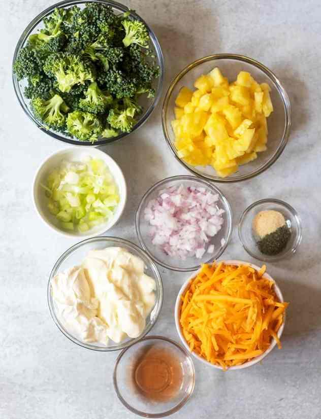 broccoli florets, diced pineapple, green onions, red onions, mayo, sour cream, cheddar cheese, vinegar, seasonings
