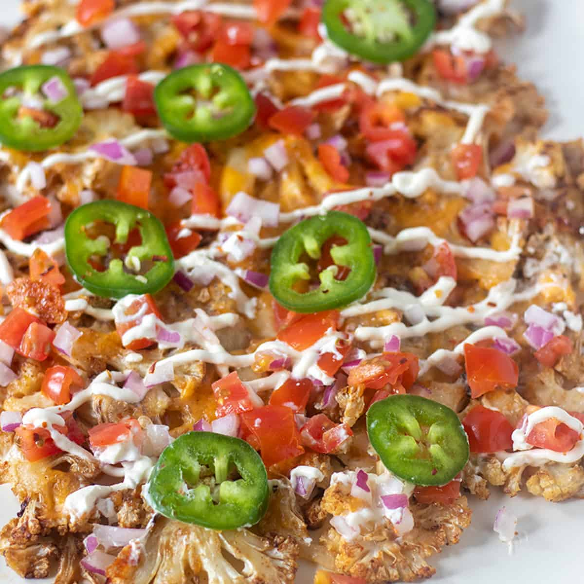 Cauliflower nachos topped with melted cheese, tomatos, onion jalapeno and sour cream