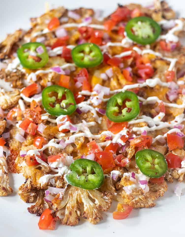 Cauliflower nachos topped with cheesy, tomatoes, jalapeno, red onion and sour cream