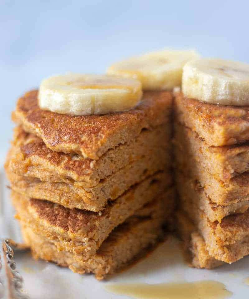 sweet potato pancakes topped with banana and maple syrup