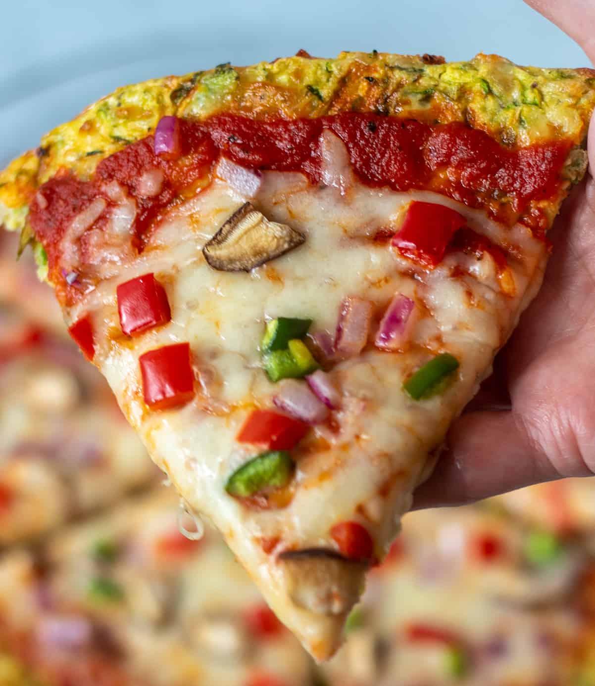 Holding slice of zucchini pizza crust in hand