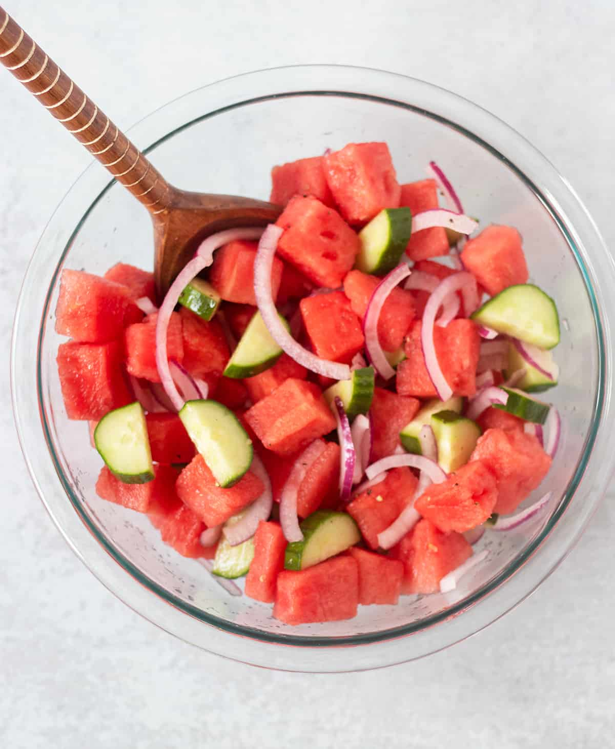 watermelon, cucumber, red onion in clear glass mixing bowl.