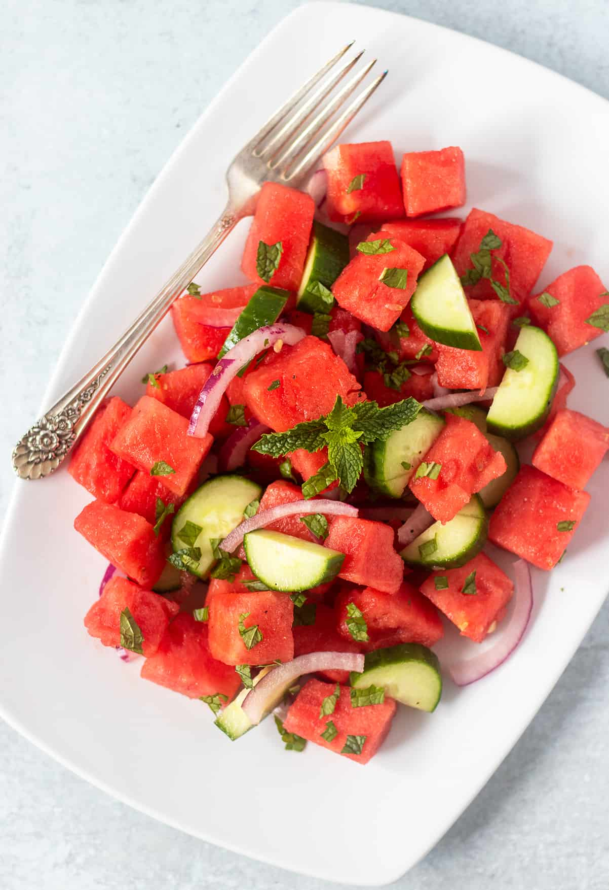 watermelon cucumber salad on white serving plate with a silver fork.