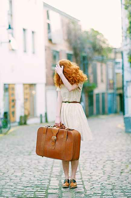 woman in white short sleeved dress holding brown leather suitcase