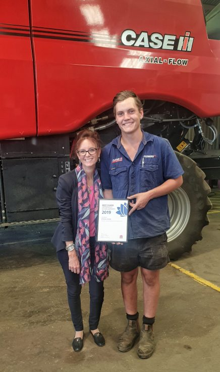 Steph Cooke MP and apprentice Agricultural Mechanic Mitchell Collins stand with his Bert Evans Scholarship in front of a huge red tractor.