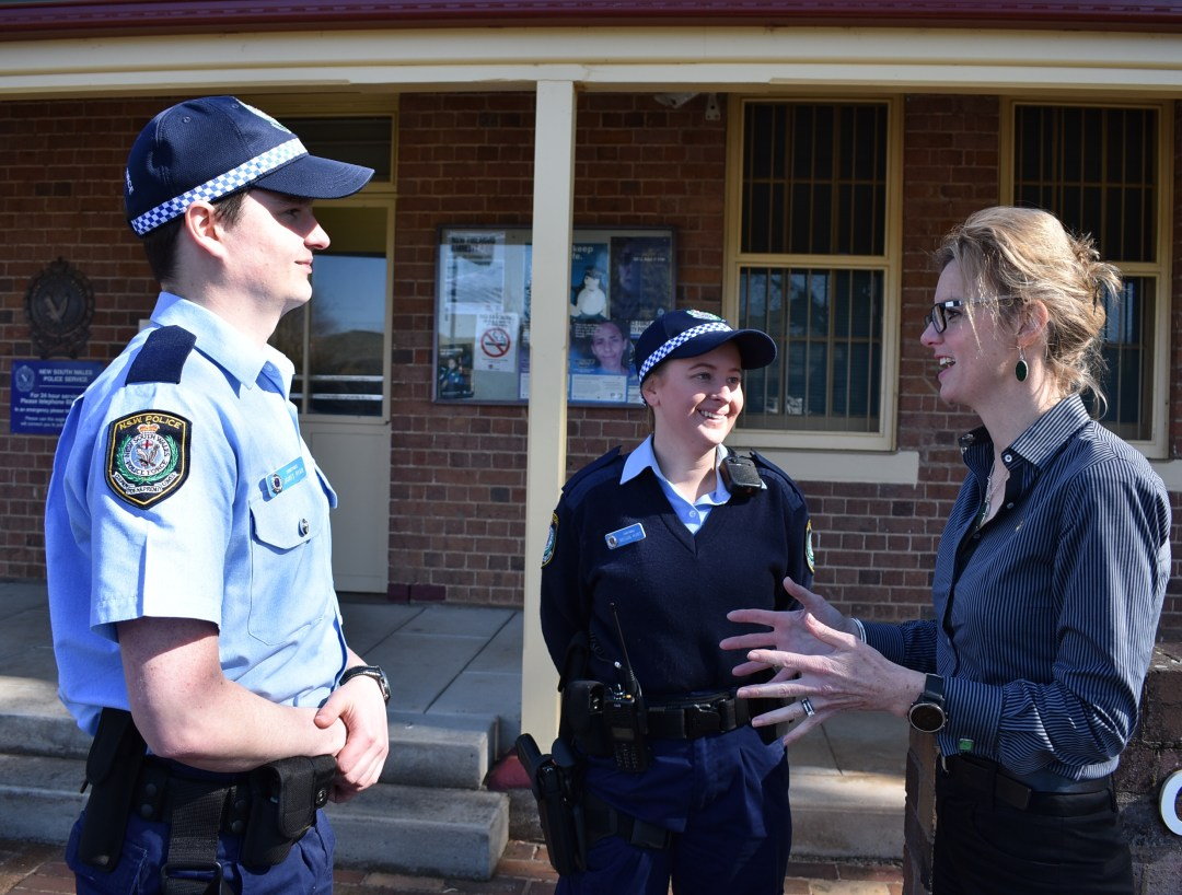 A male and a female police officer in uniform smile as Steph Cooke speaks to them outside the Cootamundra Police Station.