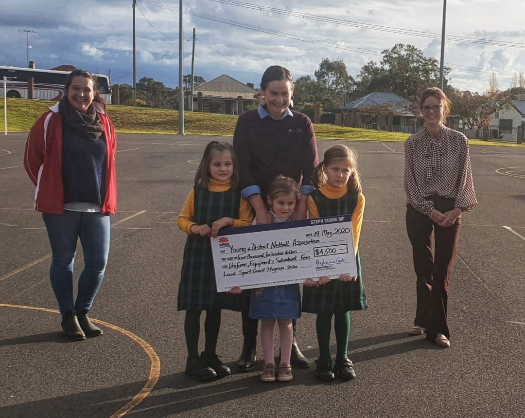 Melinda Hambrook, Pixie, Sheree, Mable and Rose Gibson with Member for Cootamundra Steph Cooke pose around a novelty cheque at the Young Netball Courts.