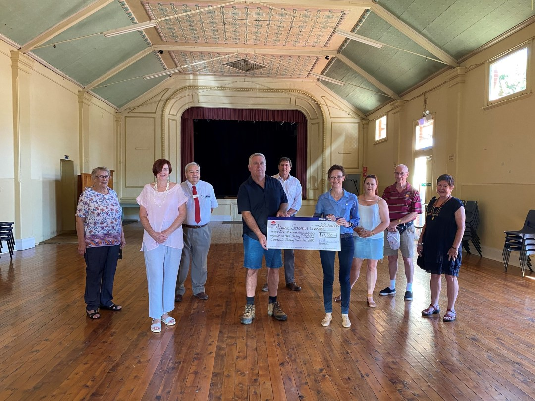 Steph Cooke and members of the Advance Ganmain Committee stand in a large hall with polished timber floors and an ornate green and coral ceiling.