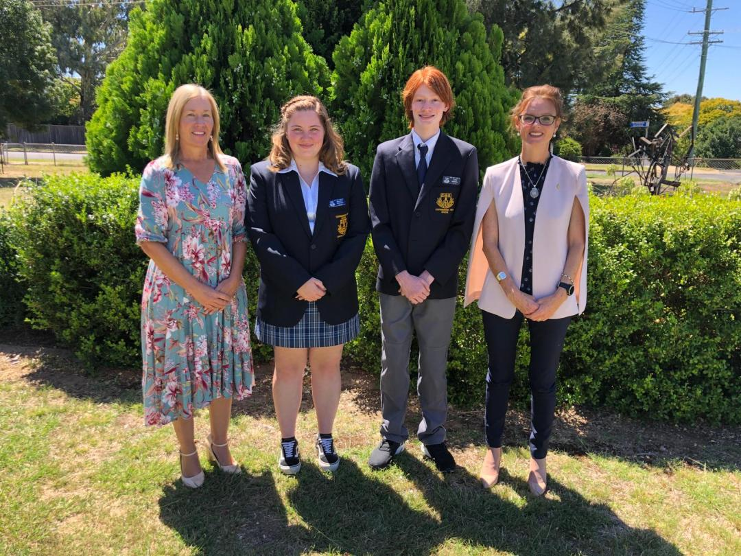 Leesa Daly, Helena Morton-Seckold and Luke Dowell and Steph Cooke stand in front of a hedge and smile at the camera. Helena and Luke wear school uniforms with blazers.