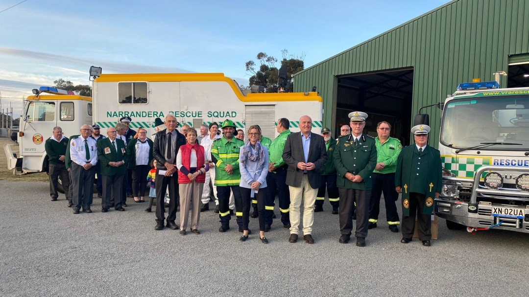 A group of people, many in green VRA uniforms, stand in front of a rescue squad truck and smile.