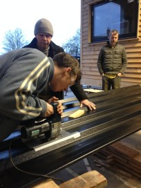 Joel and Adrian cutting hole in roof for flue under the watchful eye of Tom Stubbs