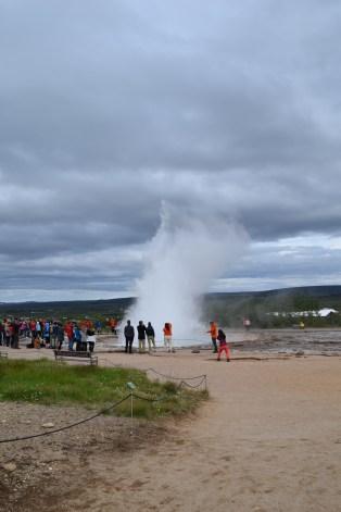 Strokkur erupts from afar.