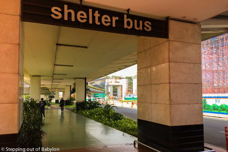 "When you leave the airport building (arrivals) you must turn left, and keep walking under the roof until the end of the arrivals building. There you will see a sign (a kind of gate) with the words ""Shelter Bus""."