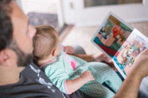 A father with a baby on his lap reading a book