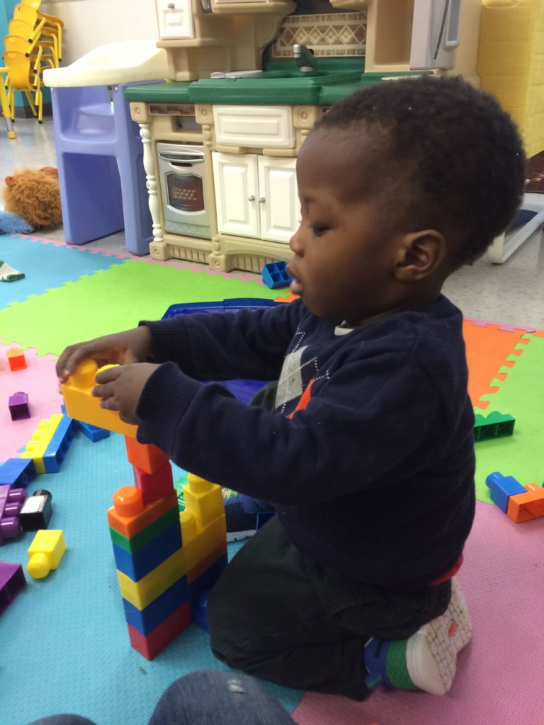 Young child building with plastic bricks at Stepping Up Daycare in West Ottawa