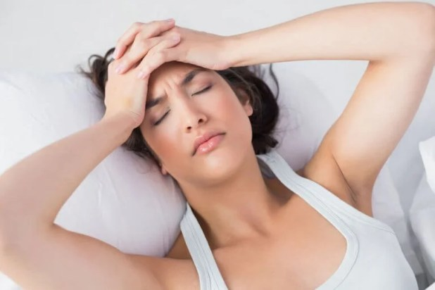 A woman in pain with a headache in bed.