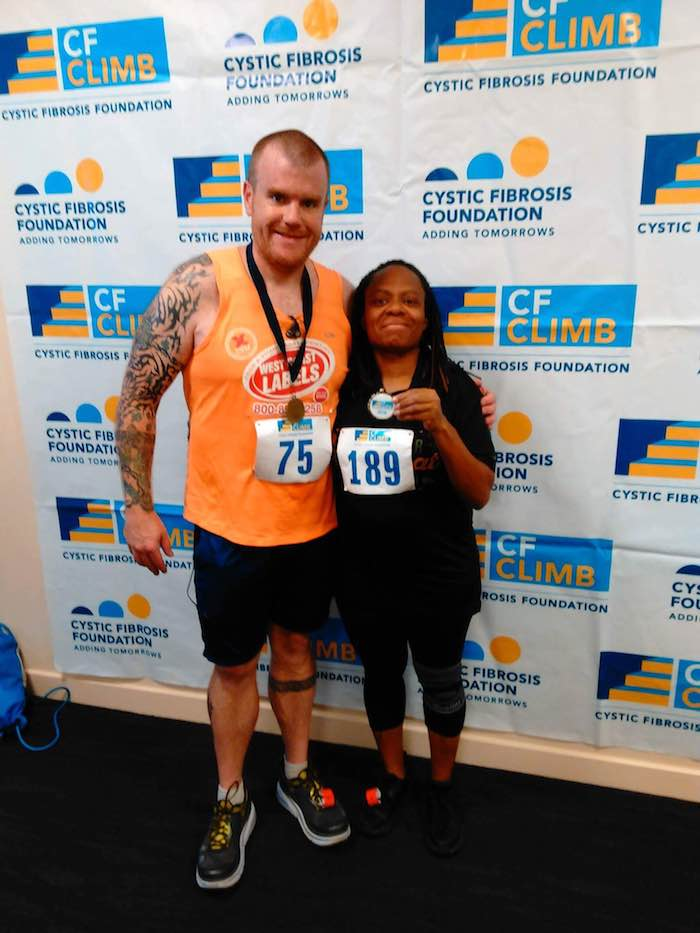 image of steve coyle after a stair climb standing with a black woman stair climber