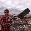 Man standing in front of landfill
