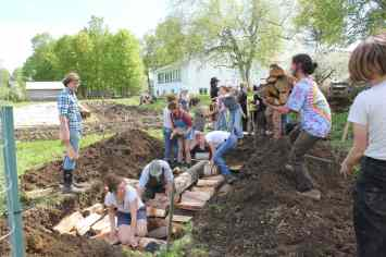 Students add dense woody material to Layer 1. Here, they're adding pruned branches from the apple trees in our Edible Forest Garden.