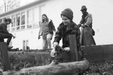 photo of smiling students working in the garden