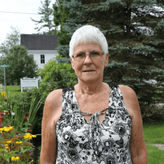 photo of Financial Aid Officer Barb Stuart, standing and smiling in front of a colorful garden and a spruce tree in summertime