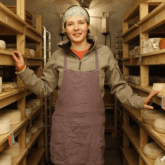 Photo of Zoe Brickley standing amongst the cheese in the cellars at Jasper Hill