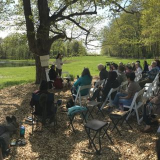 Vandana Shiva speaks to a crowd under a willow tree on a beautiful, sunny spring day on the importance of a poison free farming future