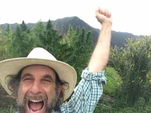 Doug Fine raises his arms in celebration standing amidst his hemp plants, with a mountain in the background