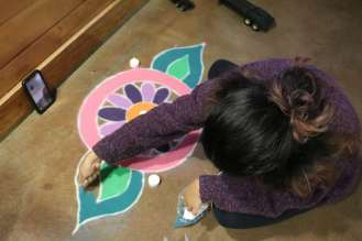 Anushka making rangoli during Diwali, which is an art form made from colored powders on the floor.