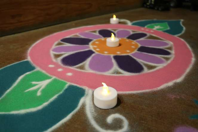 rangoli art on the floor welcoming people to the Diwali celebration.